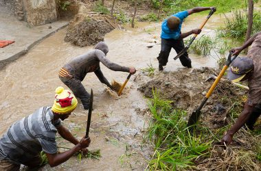 A community work brigade reroutes a muddy stream