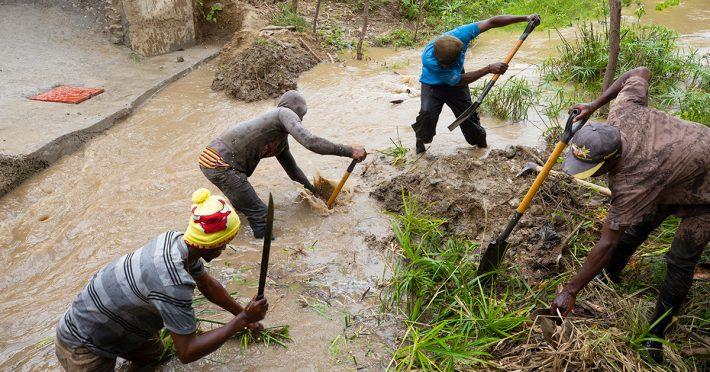 A community work brigade reroutes a muddy stream